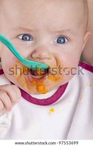 studio shot of a baby girl eating her first mashed carrot. mother feeding her baby girl with  mashed carrots