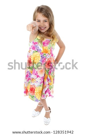Studio shot of a beautiful girl in floral designed frock pointing towards you.