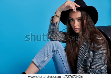 Studio shot of a beautiful young woman in a jacket, black top and jeans and a hat posing with a black barrel on a blue background.