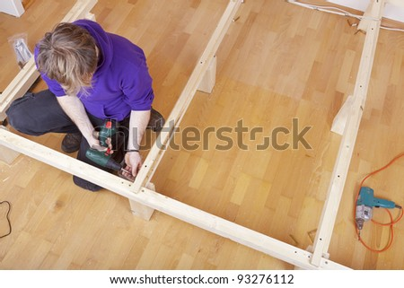 studio-shot of a carpenter at work, using a cordless drilling machine to tighten a screw into the wood. Carpenter is building a bed.