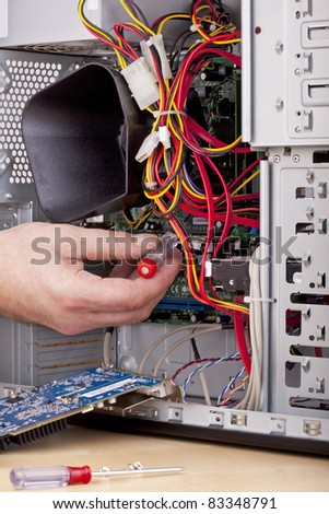 studio-shot of a computer support engineer checking the motherboard  of an office computer. - stock photo