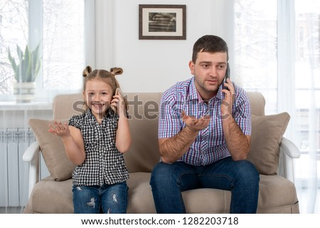 Studio shot of a daughter and dad sitting on the sofa at home and talking on the phone the same way.  Daughter imitates her father. Photo stock ©