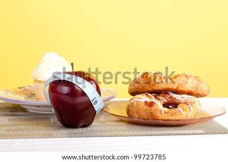 Studio shot of a delicious apple with cupcakes and pasty in the back ground with a measuring tape - stock photo