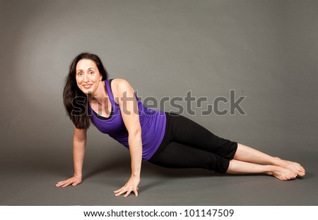 Studio shot of a fit brunette woman doing yoga stretching and flexibility exercises on a grey background
