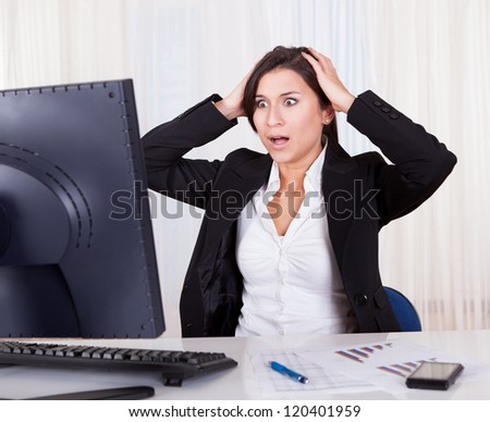 Studio shot of a frustrated businesswoman looking at her computer screen in dismay