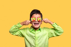 Studio shot of a funny cheerful young boy wearing green shirt closing his eyes with multi-colored round lollipops against yellow background.