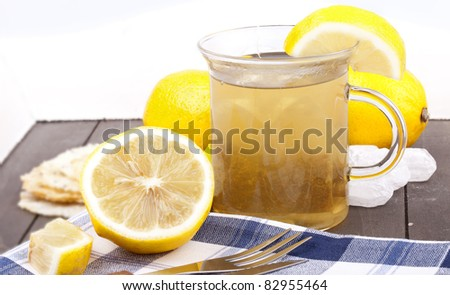 studio-shot of a glass with hot lemon tea, a slice of lemon and rock sugar, on a wooden tray.