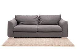 Studio shot of a grey sofa on a carpet isolated on white background