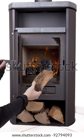 studio-shot of a hand firing a modern wood burning stove with firewood, isolated on a white background.
