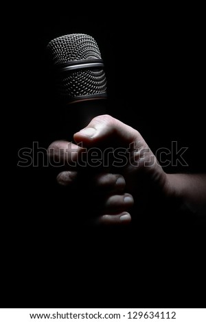 Studio shot of a hand holding a microphone, on black