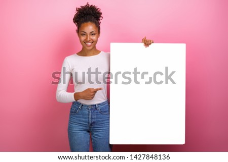Studio shot of a happy girl pointing for empty white paper sheet copyspace- Image