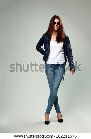 Studio shot of a happy model in leather jacket and sunglasses on gray background