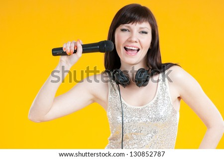 Studio shot of a happy young woman singing with a microphone