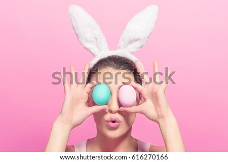 Studio shot of a happy young woman wearing bunny ears and holding up a colorful Easter egg in front of her eye