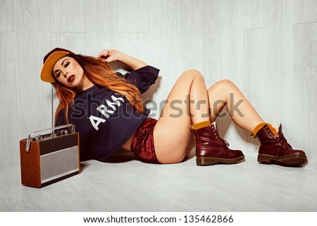 Studio shot of a hot brunette model lying on the floor, listening to an old radio.