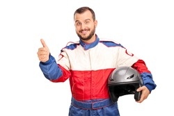 Studio shot of a joyful car racer in a racing uniform holding a helmet and giving a thumb up isolated on white background
