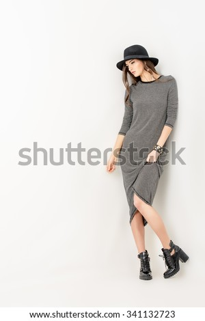 Studio shot of a magnificent young woman in a fitting dress and elegant classic hat. Beauty, fashion concept. Full length portrait.