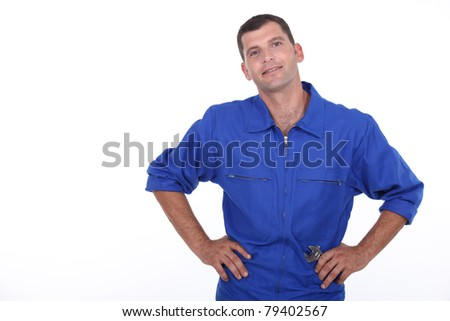 Studio shot of a man in blue overalls with his hands on his hips