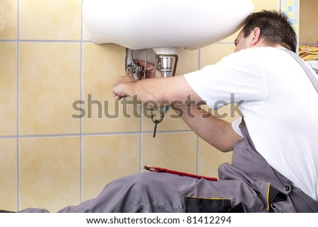 studio-shot of a plumber repairing the drain of a sink.