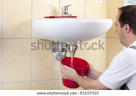 studio-shot of a plumber repairing the drain of a sink and changing a clogged pipe. the plumber is flushing the drain. - stock photo