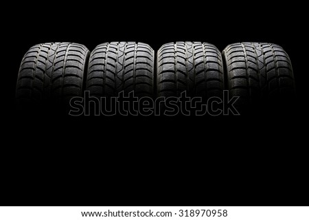 Studio shot of a set of four black car tires lined up horizontally in a dark ambient on black background