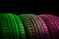 Studio shot of a set of summer car tires in green and pink tones. Tire stack background. Car tyre protector close up. Black rubber tire. Brand new car tires. Close up tyre profile. Car tires in a row