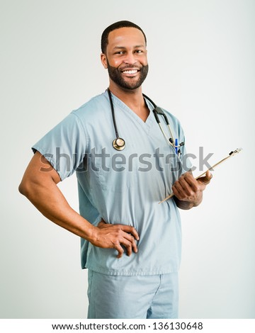 Studio shot of a young African American doctor or nurse holding a clipboard.