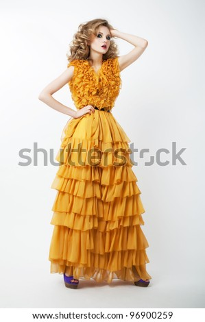 Studio shot of a young beauty woman wearing fashion luxury yellow bright dress