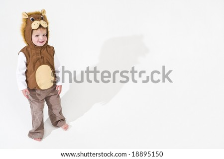 Studio shot of a young blond boy dressed as a lion with a big shadow stretching out behind him