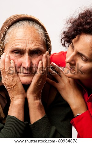 Studio shot of a young woman consoling her old mother
