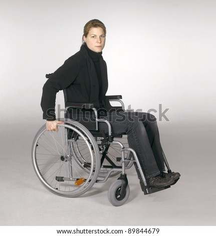 studio shot of a young woman in a wheelchair in light grey back