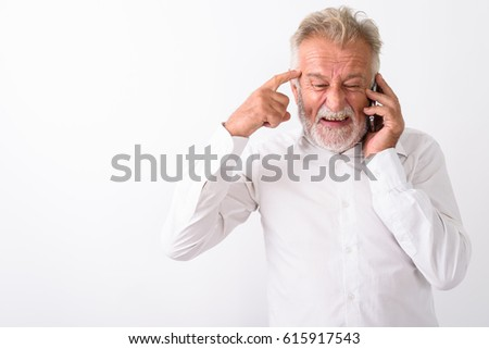 Studio shot of angry senior bearded man thinking while talking on mobile phone against white background #615917543