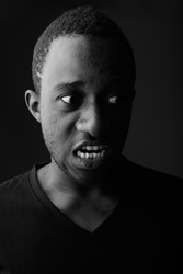 Studio shot of angry young black African man screaming in dark room