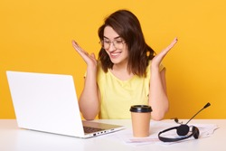 Studio shot of attarctive girl working with lap top while sitting at white desk, looking smiling at computer screen and spreading hands, isolated over yellow studio background. Technology concept.