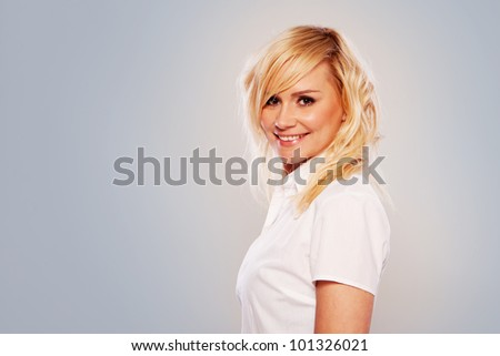 Studio shot of attractive blonde in white shirt on gray background with copy space