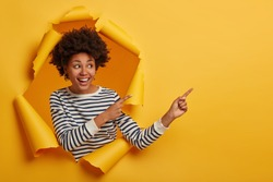 Studio shot of attractive curly girl ?n striped jumper points aside on blank space with both index fingers, stands in paper hole of yellow background, happy to show cool promotion or advert.