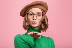Studio shot of attractive gorgeous woman in spectacles blows sweet kiss at camera, flirts with boyfriend, says goodbye. Adorable female sends kiss to you. People, farewell, relationship concept