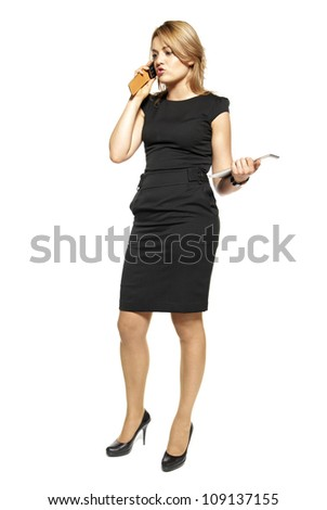 Studio shot of attractive  woman in a black dress. Woman talking on the phone.