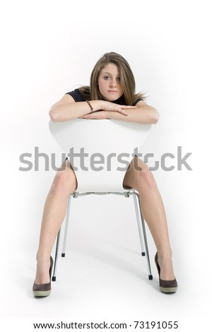 Studio shot of beautiful blonde caucasian girl facing camera on a white chair over white background.