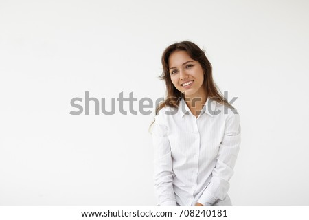 Studio shot of beautiful Hispanic female college student wearing white shirt having cheerful look, standing against blank wall background with copy space for your text or advertising content. #708240181