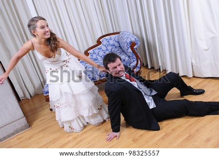 Studio shot of bride and groom. She drags him to the marriage