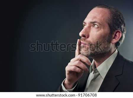 Studio shot of businessman in a deep thought over colored background