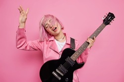 Studio shot of carefree female musician performs favorite music keeps arm raised has pink hair floating on wind holds black acoustic guitar enjoys rock n roll dreams to become famous artist.