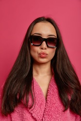 Studio shot of cheeky fashionable brunette lady has rounded lips, wears sunglasses and warm coat, has elegant look, going to have walk, poses against pink background. Fashion and style concept