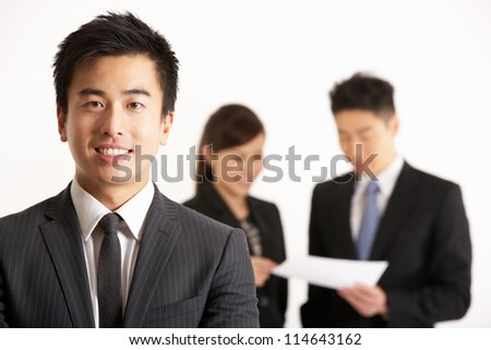 Studio Shot Of Chinese Businesspeople Discussing Document