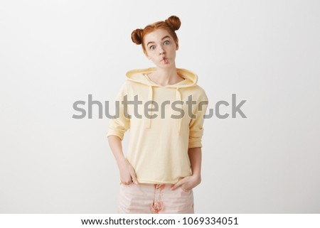 Studio shot of cute stylish young redhead with two buns making fish face with folded lips, popping eyes at camera, mimicking and making fun, standing childish against gray background