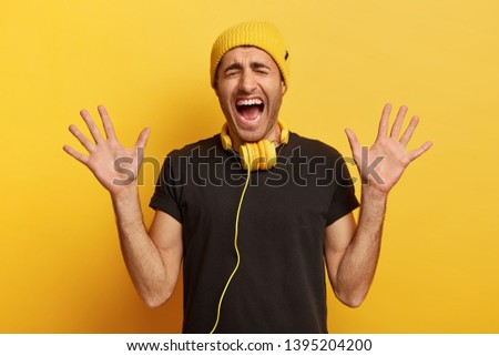 Studio shot of emotional hipster guy shouts and gestures actively, shows palms at camera, screams from negative emotions, listens music in headphones, models over yellow background. Lifestyle #1395204200