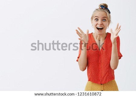 Studio shot of emotive and joyful girl seeing something tremendous waving raised palms smiling broadly and gazing at surprising and exciting thing over gray background, being amused and entertained
