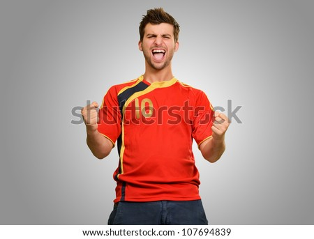 Studio Shot Of Excited Young Player Isolated On Grey Background