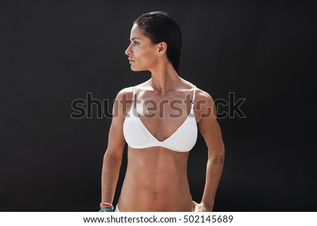 Stock Photo Studio shot of fitness woman in white lingerie looking away at copy space over black background. Muscular young woman in swimwear.
